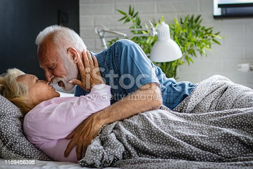 154918758 istock photo The old senior couple are kissing in bed 1159456398
