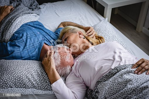 istock The old senior couple are kissing in bed 1159460483