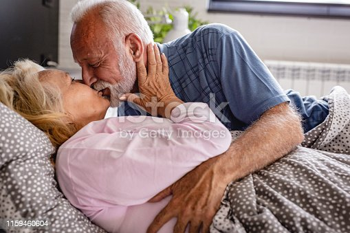 154918758 istock photo The old senior couple are kissing in bed 1159460604