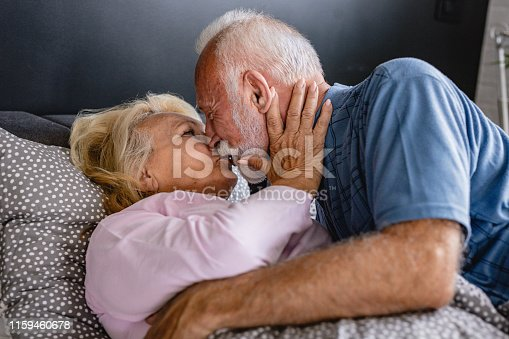 154918758 istock photo The old senior couple are kissing in bed 1159460678