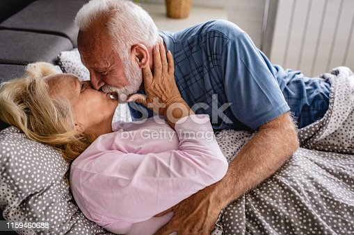 Senior couple lies in bed. senior man kisses senior woman in the morning