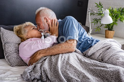 istock The old senior couple are kissing in bed 1159460703