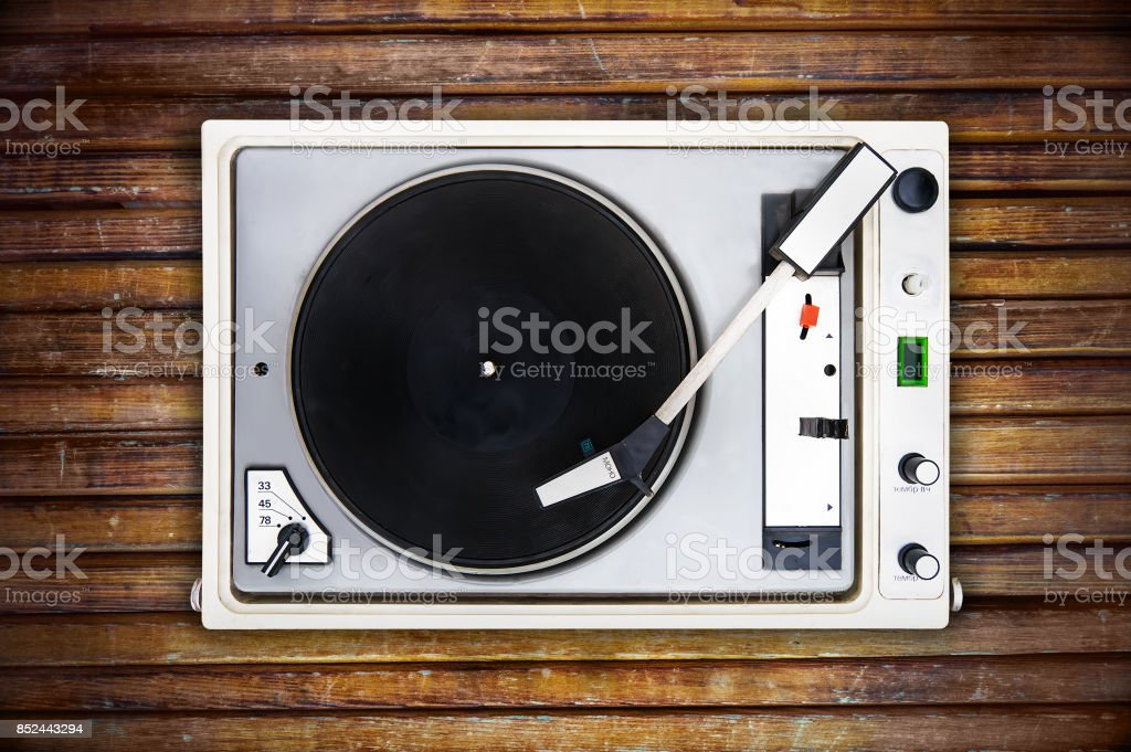 The old Soviet vinyl player isolated on wooden background. – zdjęcie