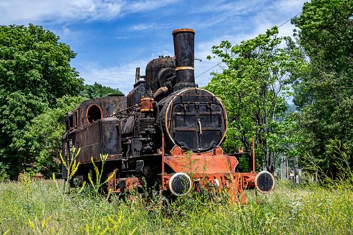  Petrosani, Hunedoara, Romania –  July 11, 2021: The old steam locomotive is parked in a depot in Petrosani, Romania