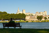 Avignon,France-06 20 2015:Couple of people admiring beyond the Rhône river,the old medieval city of Avignon and its well known Palace of the Popes.Once a fortress and palace, the papal residence was the seat of Western Christianity during the 14th century.Since 1995, the Palais des Papes has been classified, along with the historic center of Avignon, as a UNESCO World Heritage Site.