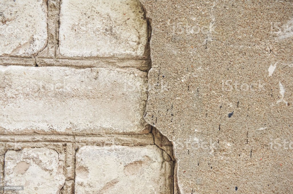 The old wall of white brick with a broken, cracked plaster. Abstract background. royalty-free stock photo