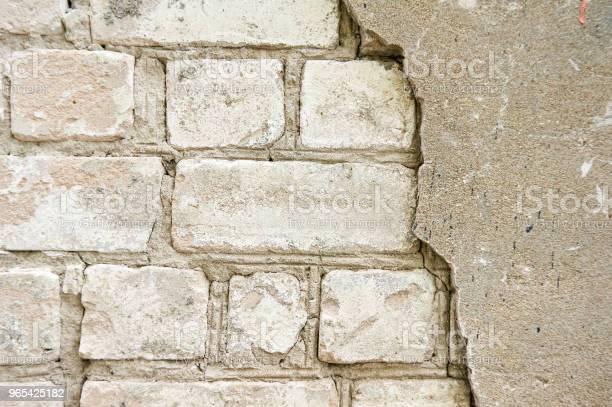Foto de O Velho Muro De Tijolo Branco Com Um Quebrado Rachado De Gesso Abstrato e mais fotos de stock de Antigo