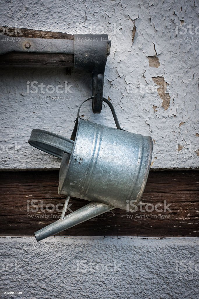 The old watering can and rocker on wall of  farmhouse stock photo