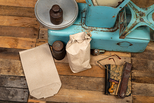 The old weight to weigh commodities from the communist era. Shop accessories on a stolen table. Dark background.