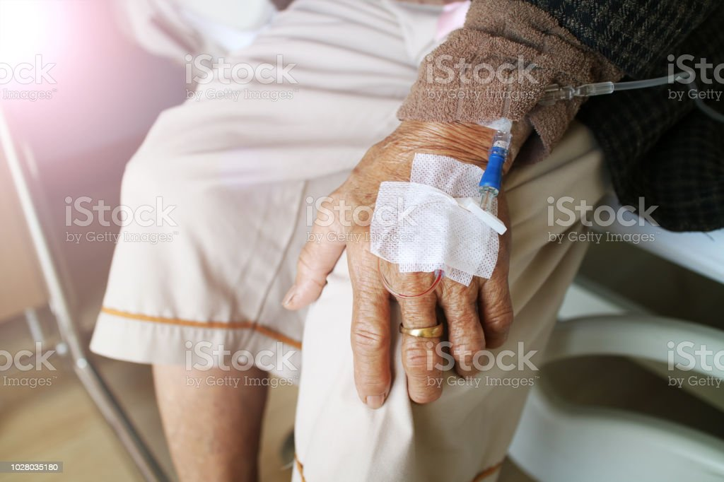 The old woman with saline solution in hospital. Grandmother resting at hospital bed with intravenous saline solution. stock photo