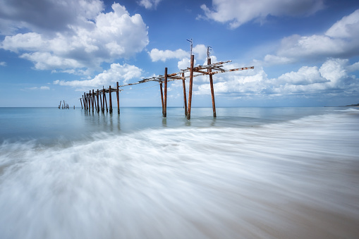 The old wooden bridge and sea wave on the beach at sunny sky background at Pilai beach, Phangnga, Thailand