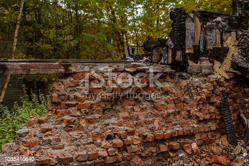 1015604978 istock photo the old wooden burned-down house a view of brick wall from inside 1035410640