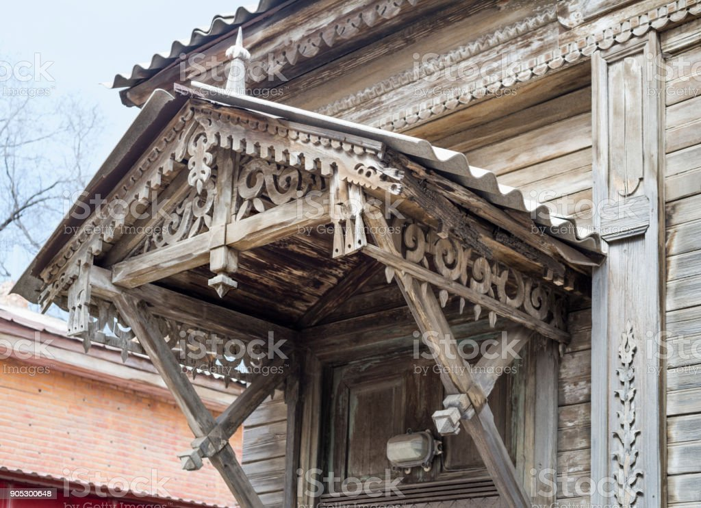 The old wooden canopy with elements of decoration above the front door