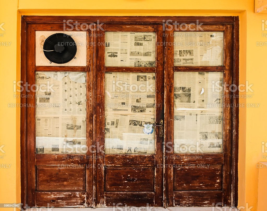 The old wooden door with old newspapers on the glass royalty-free stock photo