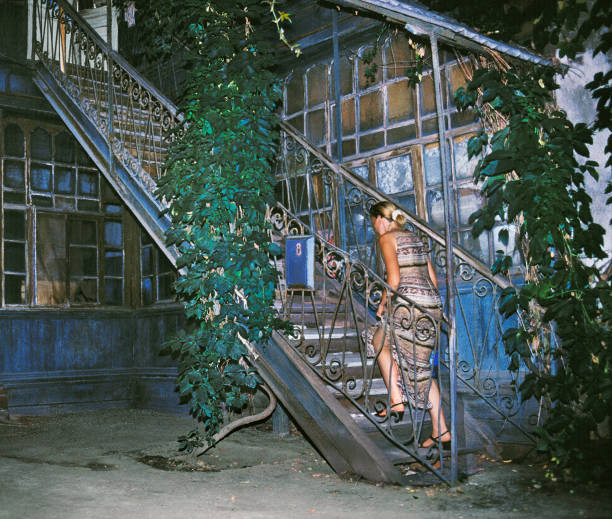 der alte hof des russischen hauses, steigt eine frau die treppe in den zweiten stock. - typisch 90er stock-fotos und bilder