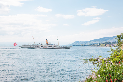 The oldest Belle Epoque steam paddle boat Montreux approaching Swiss Riviera shore in Montreux , Vaud, Switzerland