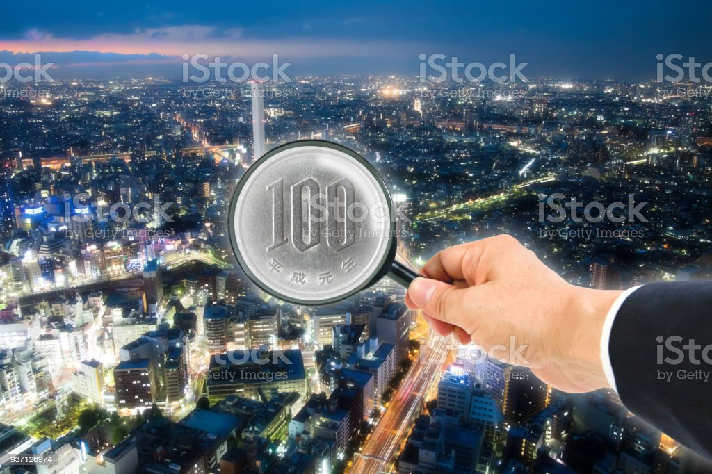The one hundred yen coin in magnifying glass stock photo