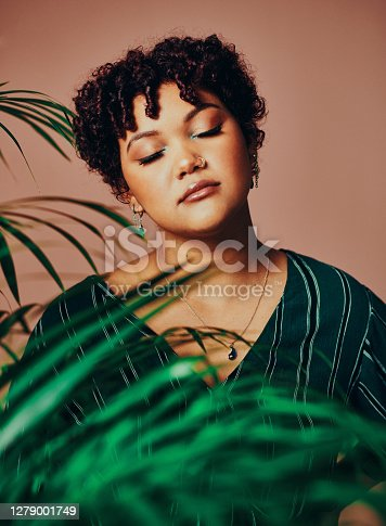 Shot of a beautiful young woman posing behind an indoor palm tree