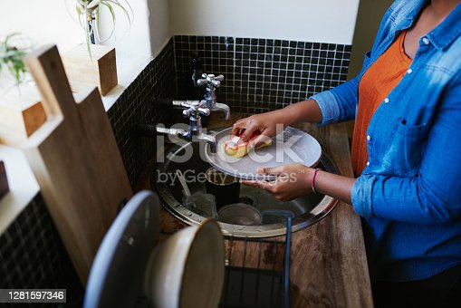 Cropped shot of a young woman washing the dishes at home