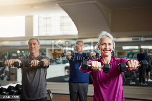 Shot of a senior group of woman and men working out with weights together at the gym