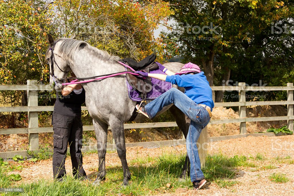 The only way is up!-girl struggles to mount horse. stock photo