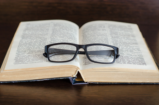 The open book lies on dark wooden table, glasses are on the book. Home schooling concept.