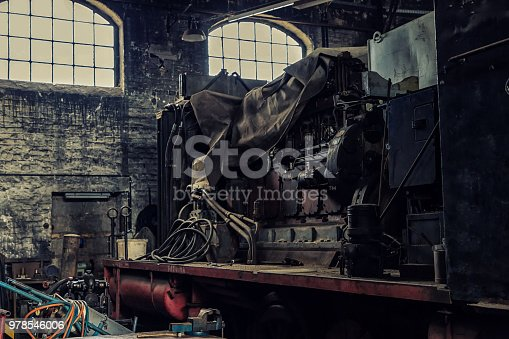 The open engine of an old electric locomotive in an abandoned workshop.