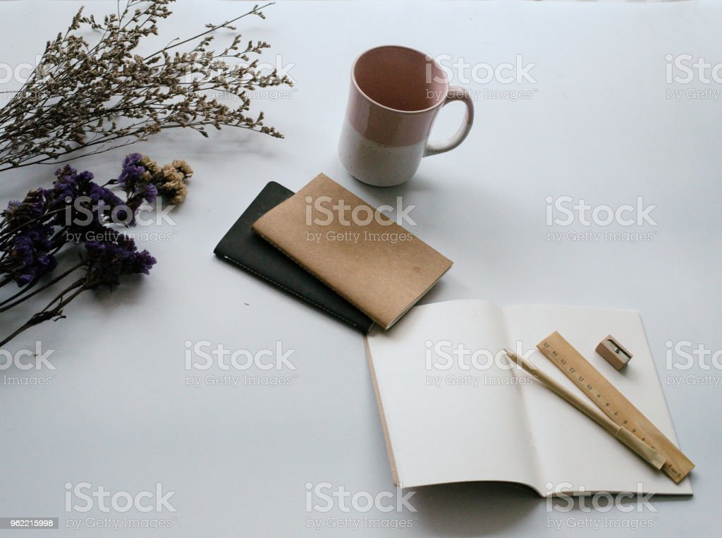 the opened book with pen and wooden ruler put beside book stacked and ceramic coffee cup on white desk stock photo
