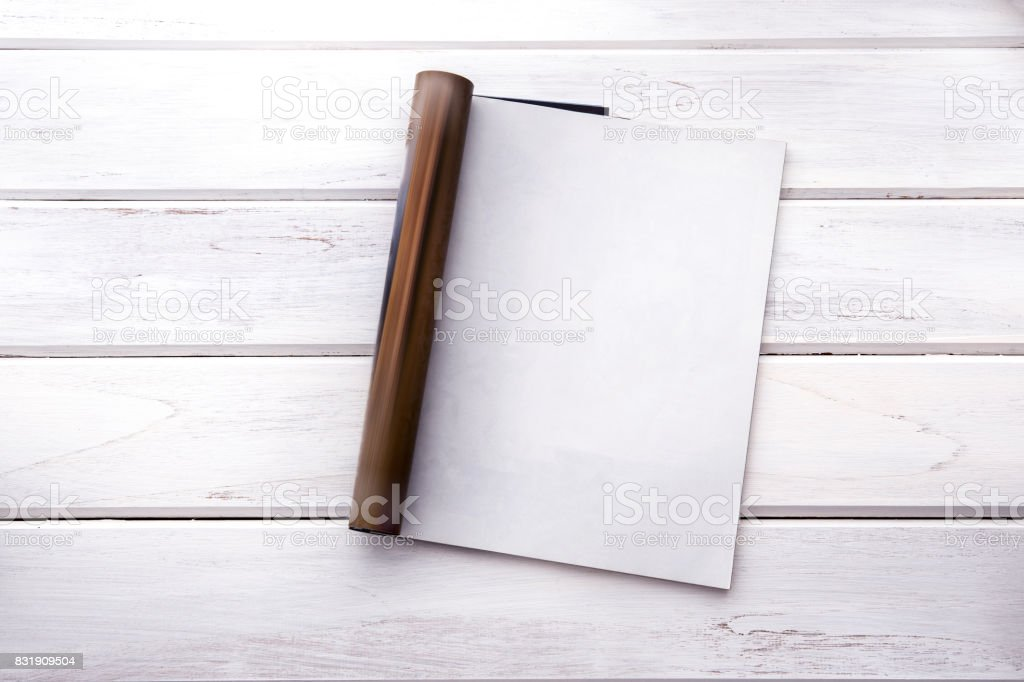 The Opened empty white mock up magazine page on white wooden table background stock photo