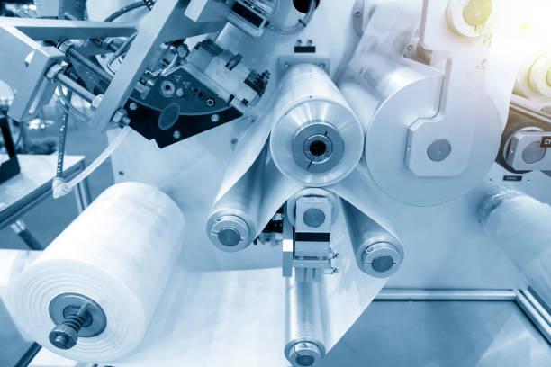 der betrieb der automatischen kunststoffbeutel-produktionsmaschine mit lichteffekt. - windbeutel stock-fotos und bilder