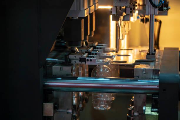o funcionamento do processo de sopro na fábrica de bebidas de garrafa de plástico. - moldando - fotografias e filmes do acervo
