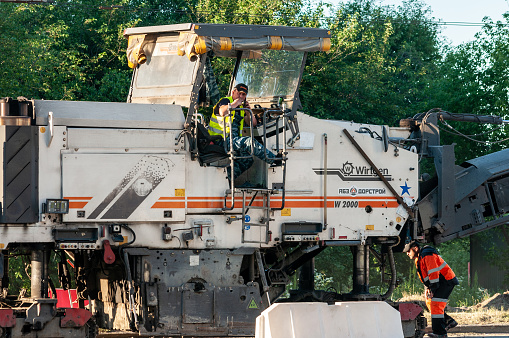 Petrozavodsk, Russia - 17 June 2020. The operator of a road milling machine is resting and smoking a cigarette