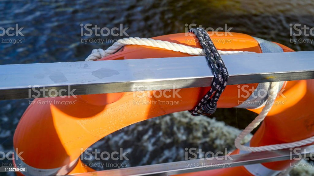 The orange bouy floater on the side of the boat stock photo