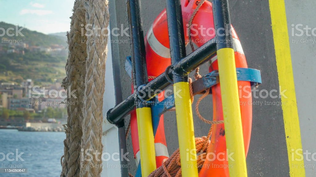 The orange bouy hanging on the gate of the ferry in Italy stock photo