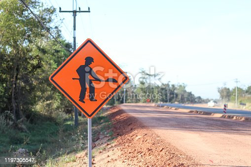 istock The orange sign shows a symbol with the image of a person holding a shovel on the sign installed on the side of the construction road. Warning sign indicating road work is ahead. 1197305547