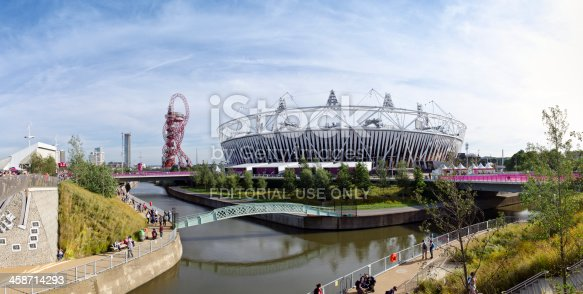 London, England - September 6, 2012: The canals of the Olympic Park in Stratford, London. The London 2012 Olympic and Paralympic Games Stadium is in the background along with the Orbit, a viewing platform. Visitors to the park can be seen walking along the canal pathways.