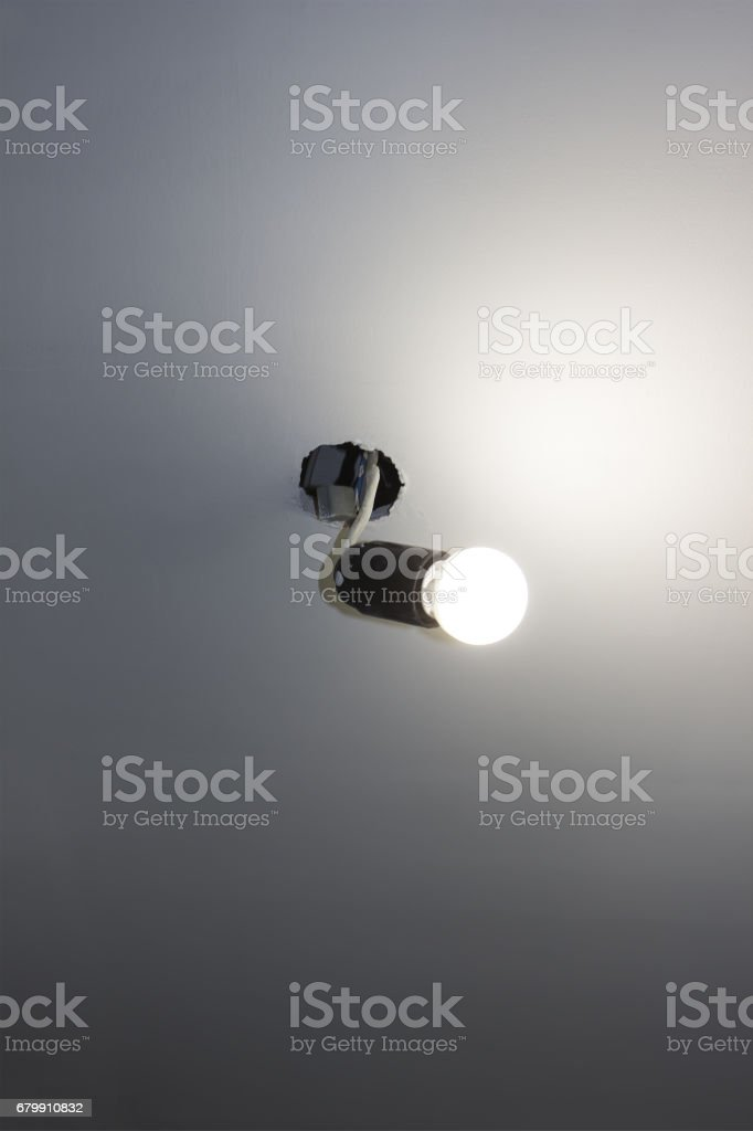 The ordinary light bulb on the wire sticks out of the ceiling stock photo
