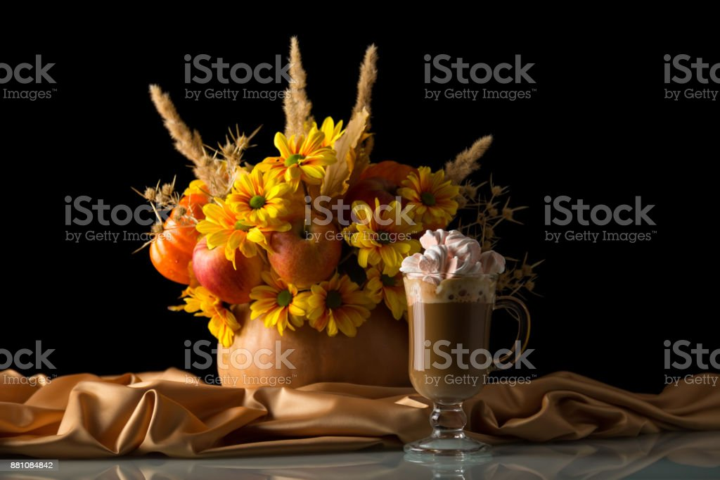 The original bouquet in the pumpkin on silk cloth, cup of cappuccino with marshmallows isolated on black stock photo