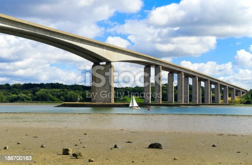 A small dinghy sailing upstream below the Orwell Bridge, which crosses the River Orwell at Wherstead, near Ipswich in Suffolk, England.