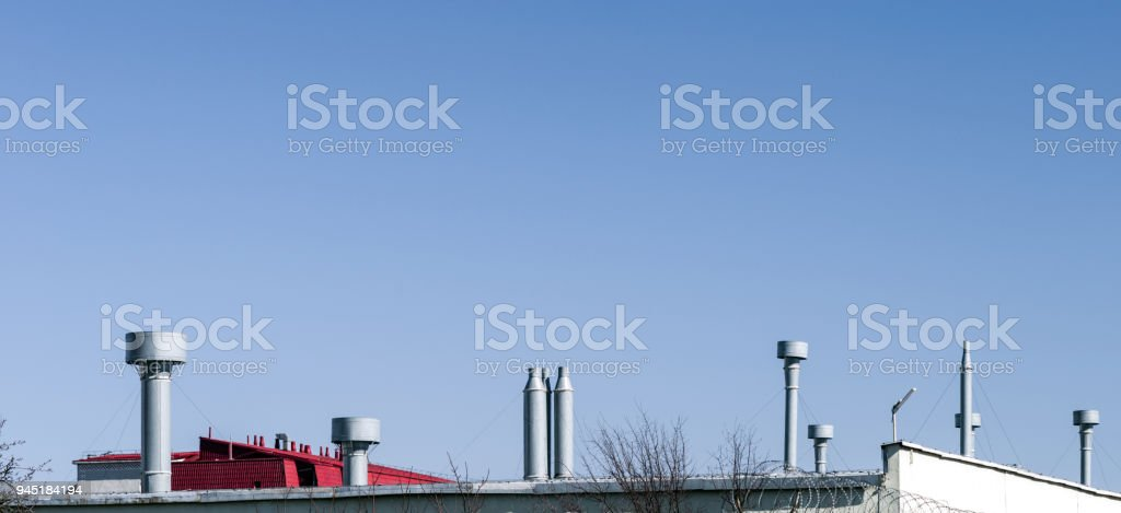 The outer tubes of the commercial air conditioning and ventilation systems are installed on the roof of an industrial building. stock photo