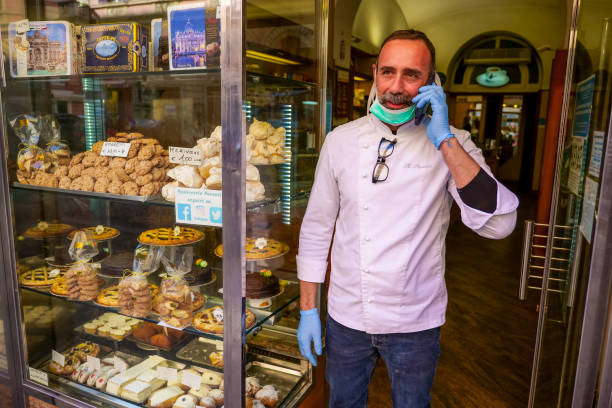 The owner of a bakery protected by a medical mask in a street in Rome stock photo