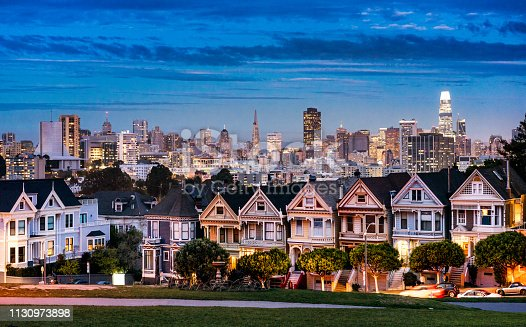 The well known row of traditional San Francisco townhouses, with the lights of downtown on the horizon in the dusky sky.