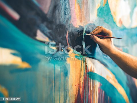Hands of Young painter working on his art inside his studio.