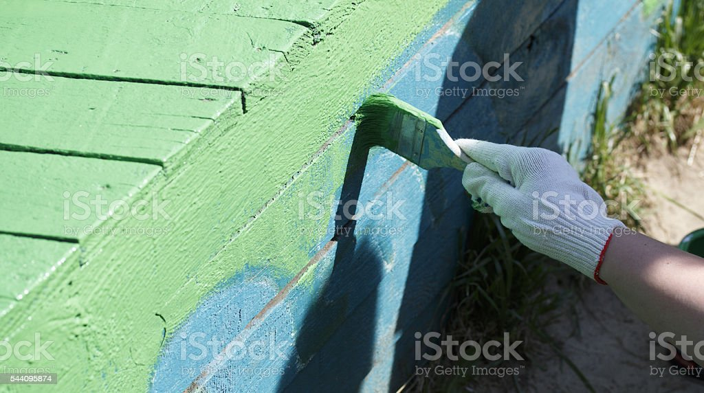 The painter paints the wooden structure stock photo