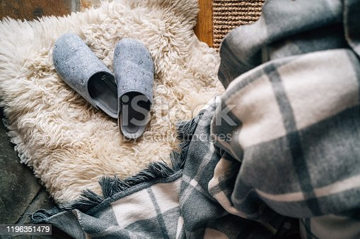 The pair of gray home slippers near the  bed on the white sheepskin in the cozy bedroom. Home sweet home concept top view image.