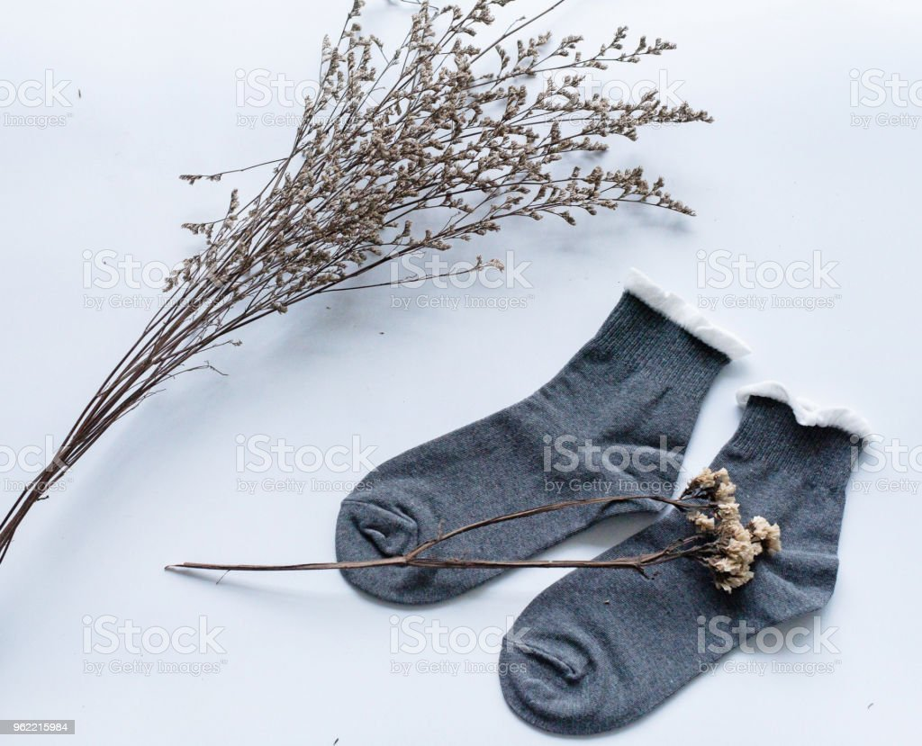 The pair of sock put at the right side on white desk,dried flower put at the left side,in abstract art design.blurry light around. stock photo