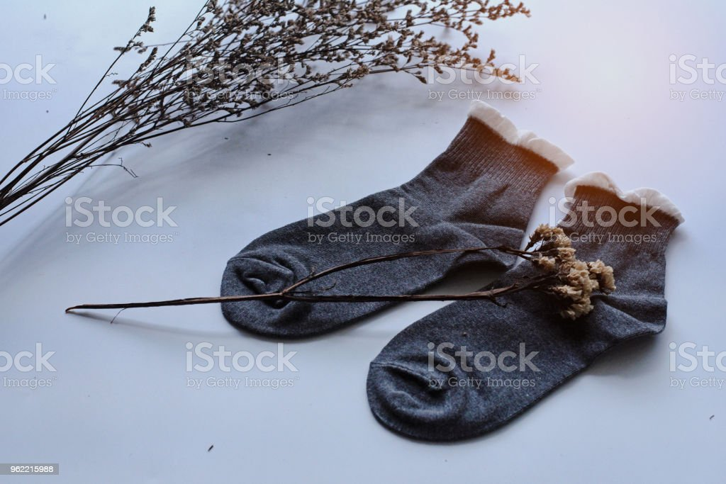 The pair of sock put beside dried flower on white desk,in abstract art design background stock photo