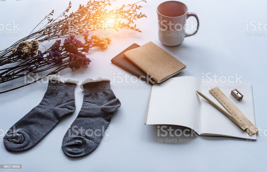 The pair of sock put beside opened book and dried flower,coffee cup put at the top right of white desk stock photo