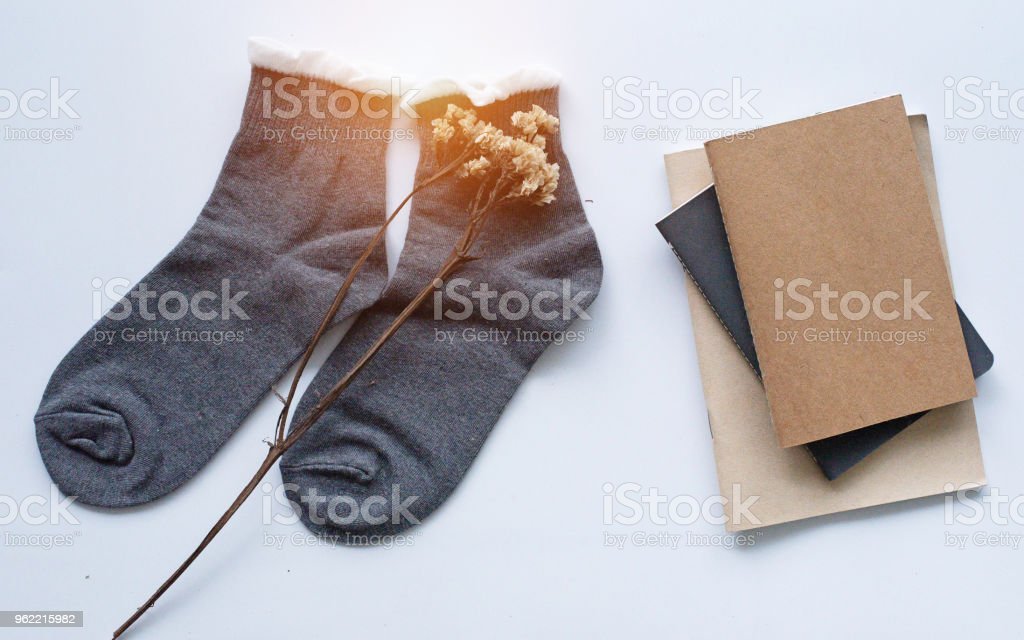 The pair of sock with dried flower put beside books stacked, on white desk,warm light tone,blurry light around. stock photo