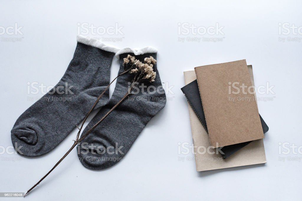 The pair of sock with dried flower put beside books stacked ,on white desk, stock photo